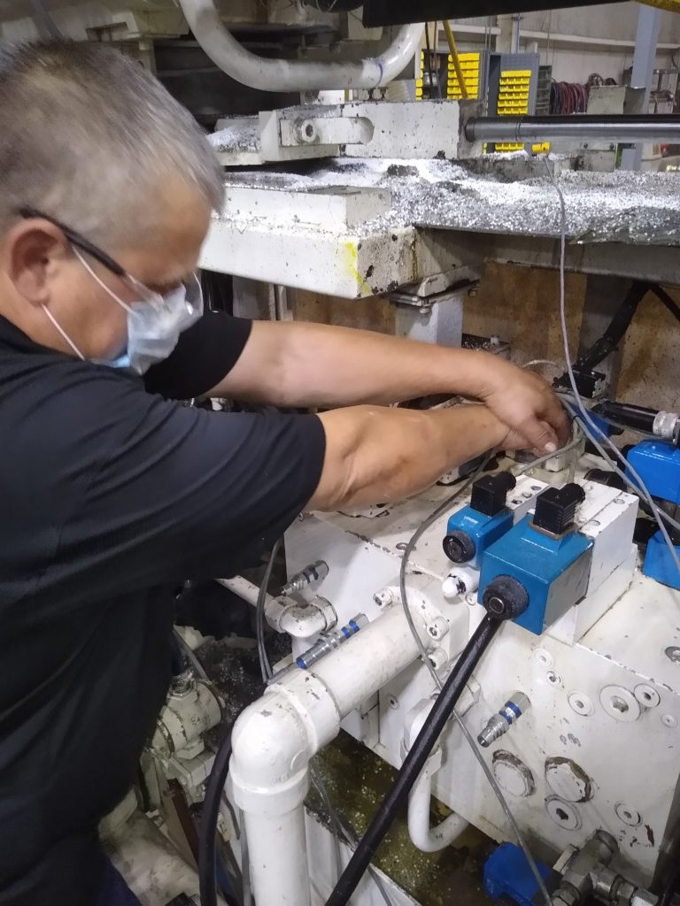 Garrett Mackenzie, Owner Plastic411 reinstalling a valve on a plastic injection manifold block.
